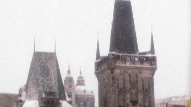 OVEREXPOSED wide shot tilt down from bridge towers to Charles Bridge, archway + buildings / Prague, Czech Republic