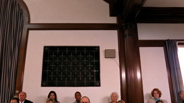 Wide shot tilt down from iron grate on wall to jury in courtroom