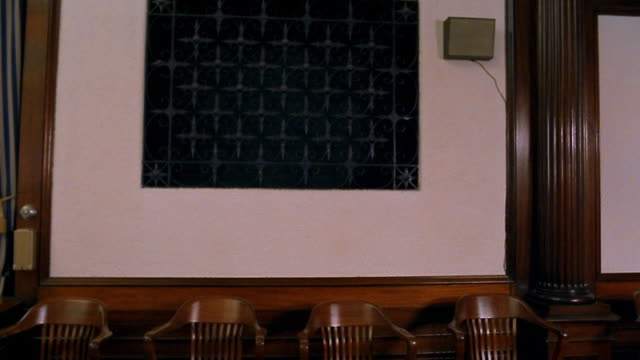 Wide shot tilt down from iron grill on wall to wooden chairs in empty jury box in courtroom
