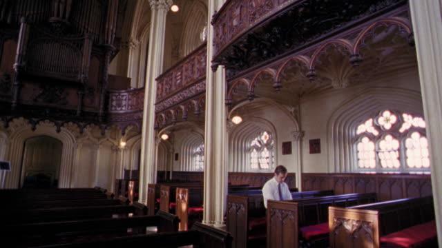 vídeos y material grabado en eventos de stock de wide shot tilt down pan from organ pipes to man sitting in church pew with head bowed / dublin, ireland - iglesia