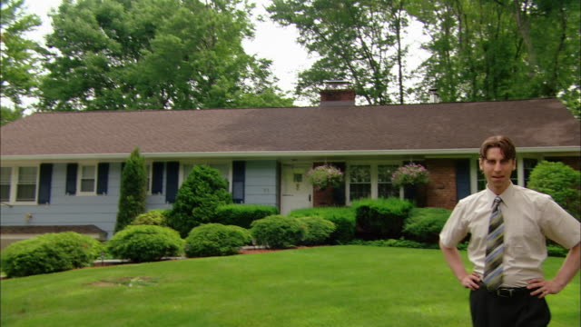 wide shot tilt down man walking on front lawn of suburban ranch house / looking at camera and sighing - ranch house stock videos & royalty-free footage