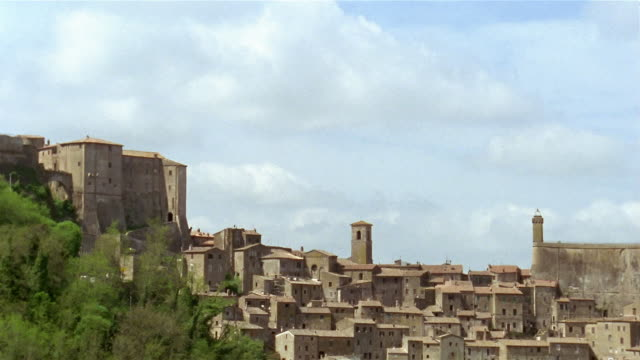 Wide shot tilt down stone houses in the hillside town of Sorano / Tuscany, Italy