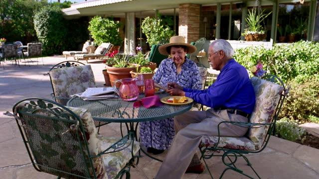vídeos y material grabado en eventos de stock de wide shot tilt down tilt up senior couple sitting on outdoor table, eating and looking at newspaper / arizona - crucigrama