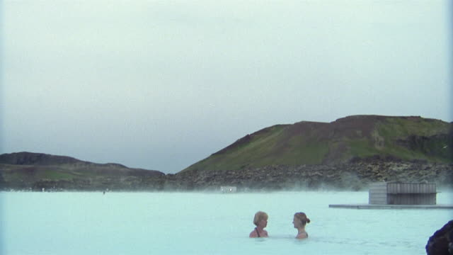 vídeos de stock e filmes b-roll de wide shot tilt down two women talking in geothermal waters of the blue lagoon (blaa loninu) / iceland - quinta de saúde