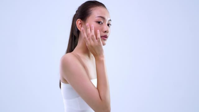 wide shot tilt up beauty girl using hand to put something on face - skin feature stock videos & royalty-free footage