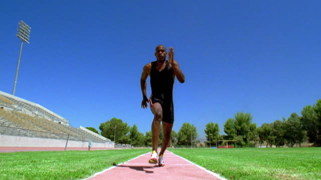 wide shot tilt up black male athlete doing lung jump over camera - salto in lungo video stock e b–roll