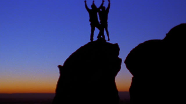 Wide shot tilt up couple raising arms and hugging at sunset atop rock in desert / New Mexico