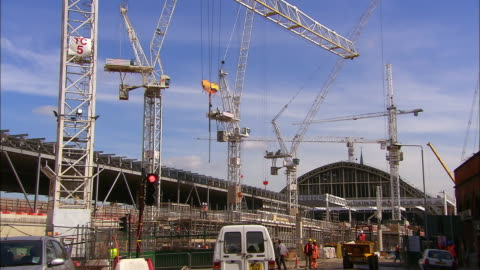 wide shot tilt up cranes at construction site of eurostar terminal / london - eurotunnel folkestone stock-videos und b-roll-filmmaterial