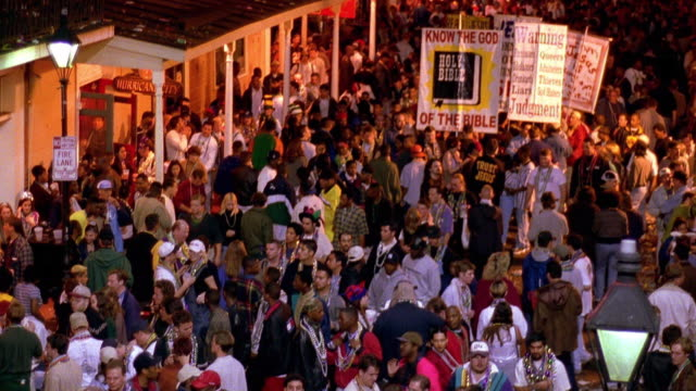 wide shot tilt up crowds of people celebrating mardi gras on bourbon street / new orleans, louisiana - new orleans mardi gras stock videos and b-roll footage