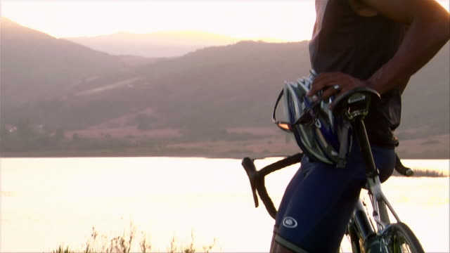 Wide shot tilt up cyclist leaning against his bike / watching the sun set over a lake