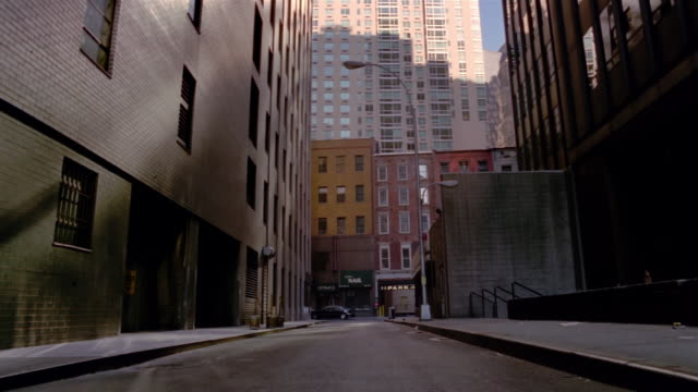 Wide shot tilt up empty street cast in shadow in Manhattan financial district / New York City