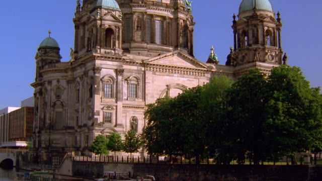 Wide shot tilt up from barge on Spree River to Berlin Cathedral (Berliner Dom) / Berlin, Germany