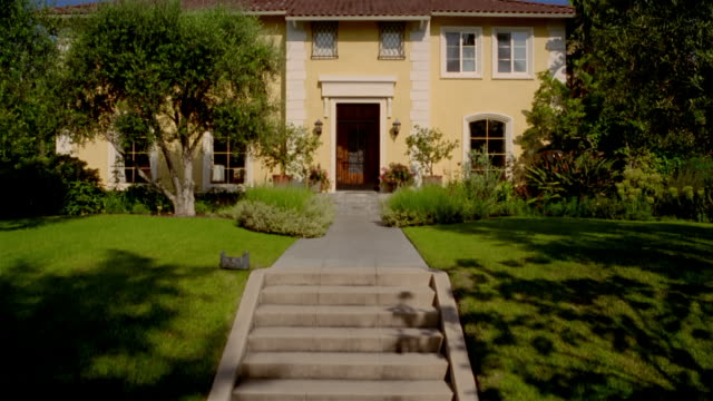 wide shot tilt up from front walkway to exterior view of yellow house with bushes and trees in front yard - establishing shot stock videos & royalty-free footage