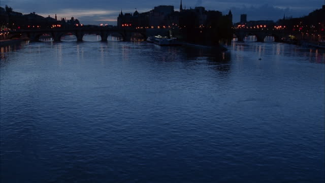 wide shot tilt up from seine river at twilight to silhouettes of pont neuf and ile de la cite / paris - back lit stock videos & royalty-free footage