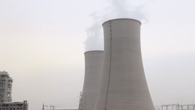 Wide shot tilt up from water reflection of vapor rising from cooling towers and a smokestack at the Sahiwal coal power plant owned by China's state...