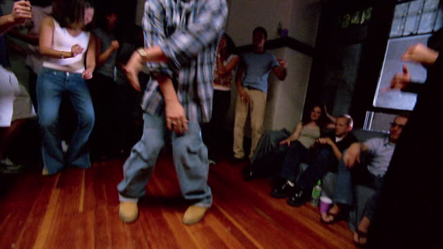 wide shot tilt up man dancing on hardwood floor with other partgoers gathered around at house party - plaid shirt stock videos & royalty-free footage