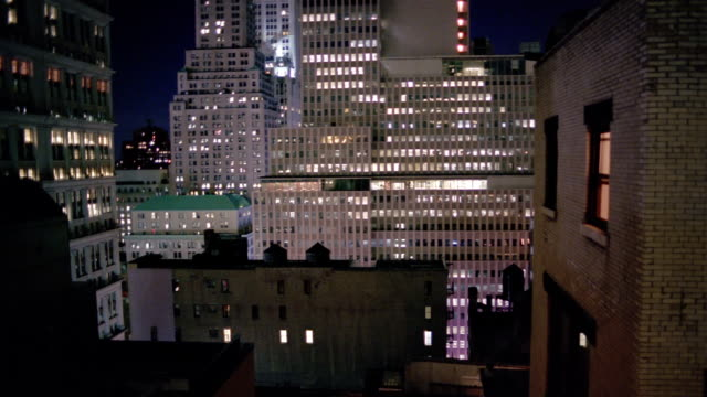 wide shot tilt up office buildings in lower manhattan lit up at night / new york city - 2005 stock videos and b-roll footage