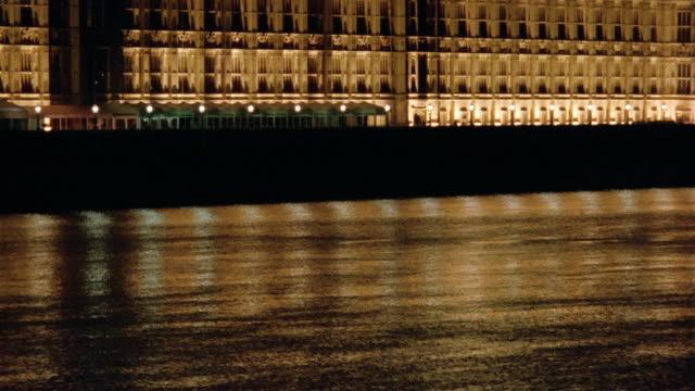 Wide shot tilt up River Thames to Westminster Palace lit up at night / London