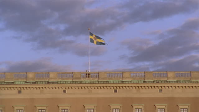 Wide shot tilt up Swedish parliament building / flag waving in the breeze / Helgeandsholmen, Stockholm, Sweden