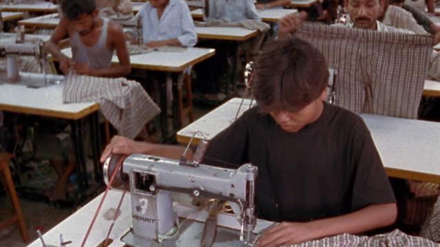 wide shot tilt up tilt down garment workers sewing plaid shorts / nepal - arbeitsintensive produktion stock-videos und b-roll-filmmaterial
