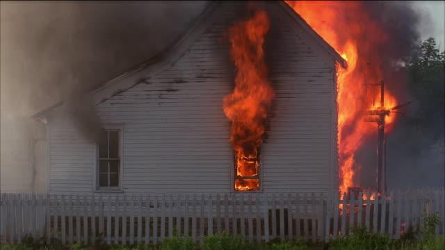 vidéos et rushes de wide shot tilt up tilt down side of house on fire - brûler