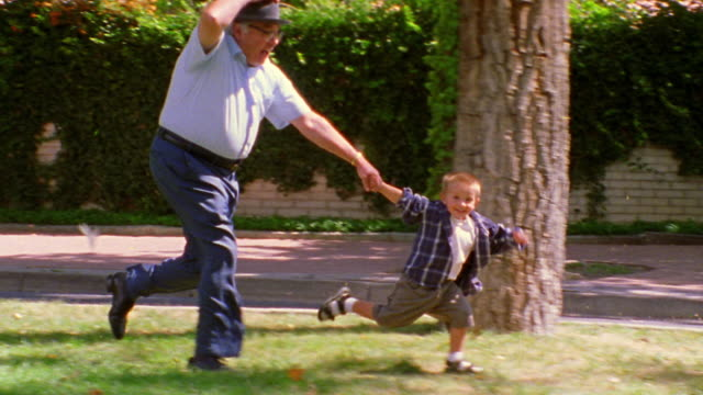 wide shot tilt up tracking shot boy holding hands with senior man + running outdoors