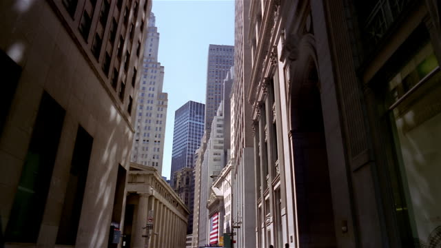 vídeos de stock e filmes b-roll de wide shot tilt up view down wall street of federal hall across street from new york stock exchange / new york - wichita