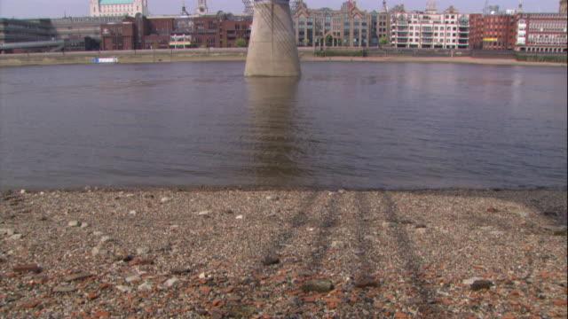 Wide Shot tilt-up - The River Thames flows under the Millennium Bridge. / London, England