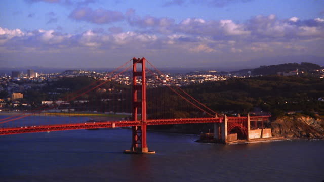 wide shot pan time lapse across san francisco bay + golden gate bridge with city in background (day to dusk) - zeitraffer tag bis dämmerung stock-videos und b-roll-filmmaterial