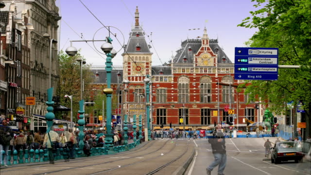wide shot time lapse automobile and pedestrian traffic around trolley track on damrak street / amsterdam - amsterdam stock videos & royalty-free footage