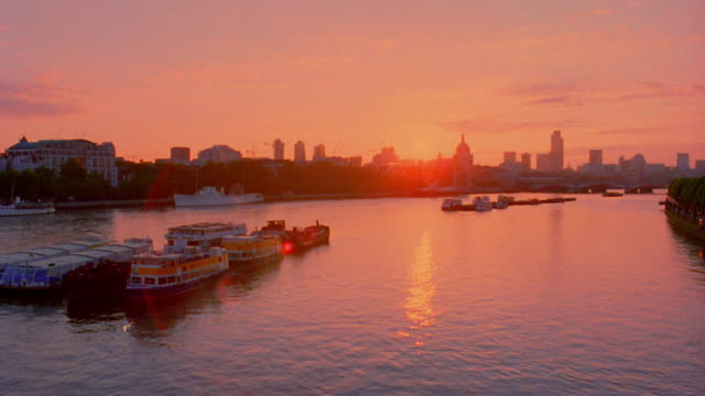 Wide shot time lapse boats docked on Thames River with London skyline in background at dawn / England