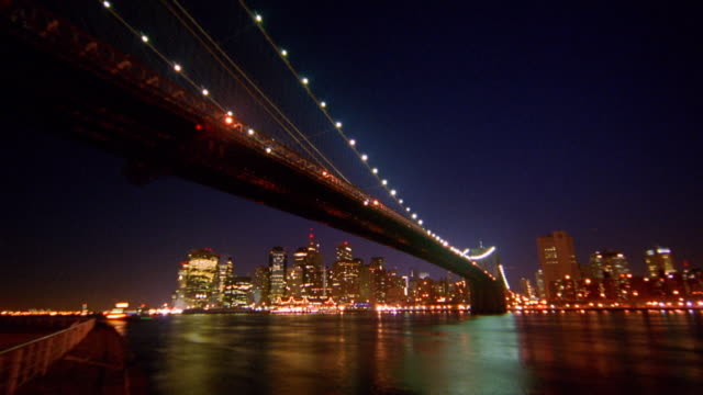wide shot time lapse boats in new york harbor and under brooklyn bridge with manhattan in background / night to dawn / nyc - east river stock videos & royalty-free footage