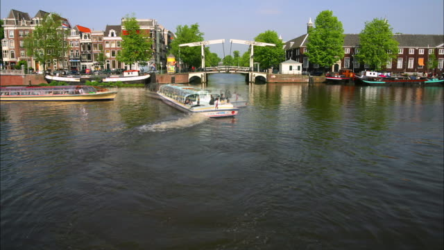 wide shot time lapse boats on the canal going under the walter suskind brug (drawbridge) / amsterdam - drawbridge stock videos & royalty-free footage