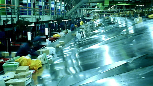 Wide shot time lapse boxes moving over conveyor belt at shipping distribution center / workers in background