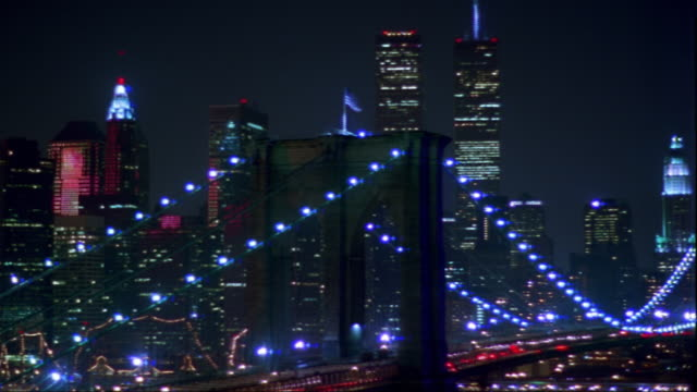 wide shot pan time lapse brooklyn bridge with fireworks reflecting on manhattan skyline in background - world trade center manhattan video stock e b–roll