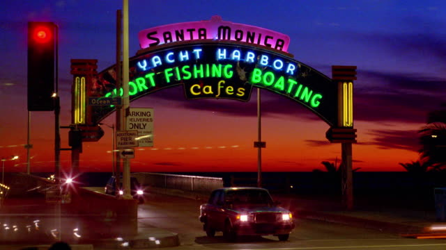 wide shot time lapse cars entering and exiting santa monica yacht harbor with neon sign over road / california - santa monica sign stock videos & royalty-free footage