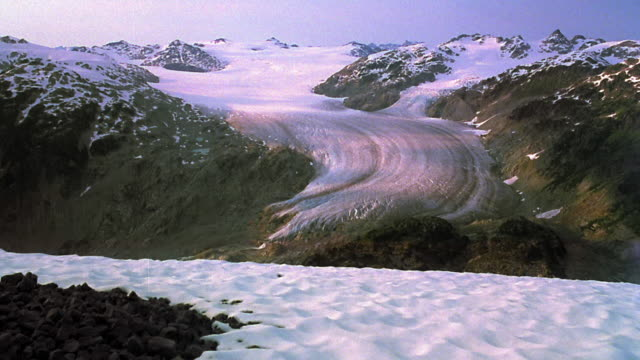 Wide shot time lapse clouds and shadows over top of glacier / Coast Mountains, Whistler, British Columbia