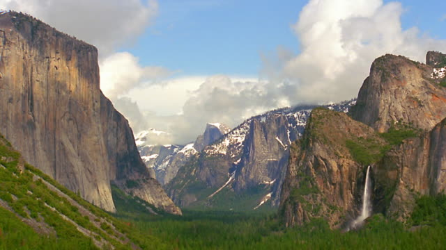 Wide shot time lapse clouds and shadows over Yosemite Valley with El Capitan + Bridalveil Falls / California