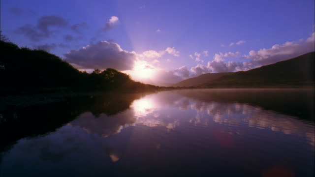 wide shot time lapse clouds and sun over mountains / croagh patrick, ireland - 2002 stock videos & royalty-free footage