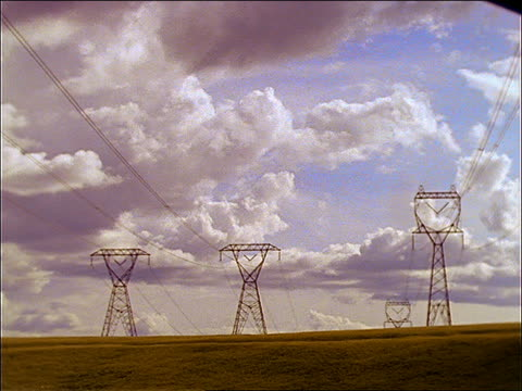 vídeos de stock e filmes b-roll de wide shot time lapse clouds in blue sky over high tension towers in field / europe - três objetos