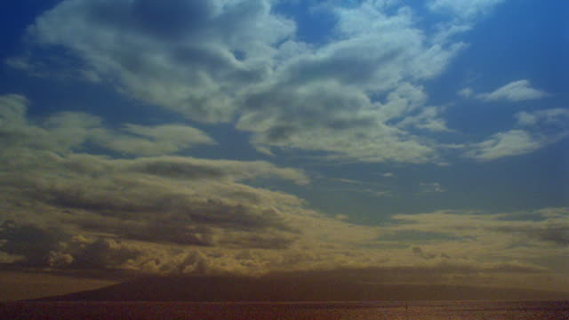 wide shot time lapse clouds in blue sky over ocean and silhouetted mountains / hawaii - 1985 stock videos & royalty-free footage