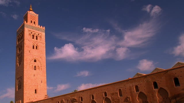 Wide shot time lapse clouds moving behind Koutoubia Mosque with bell tower / Marrakesh, Morocco