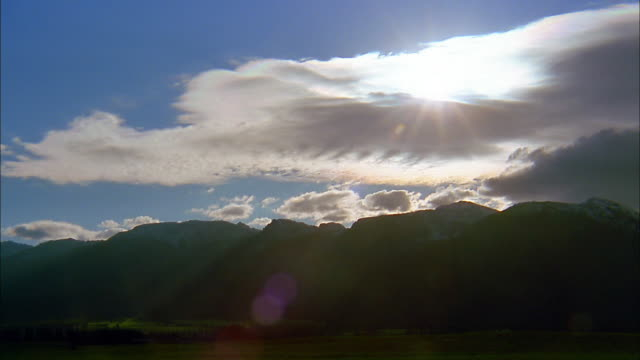 wide shot time lapse clouds moving in front of sun over silhouetted mountains - western usa stock videos & royalty-free footage
