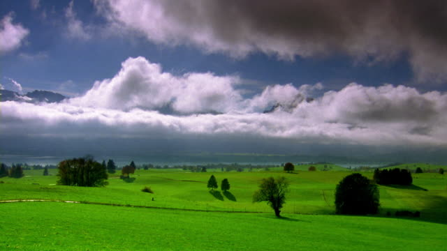 wide shot time lapse clouds moving low over green valley / lake and mountains in background / bavaria, germany - whatif点の映像素材/bロール