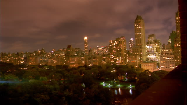 vidéos et rushes de wide shot time lapse clouds moving over illuminated buildings bordering central park at night / nyc - central park manhattan
