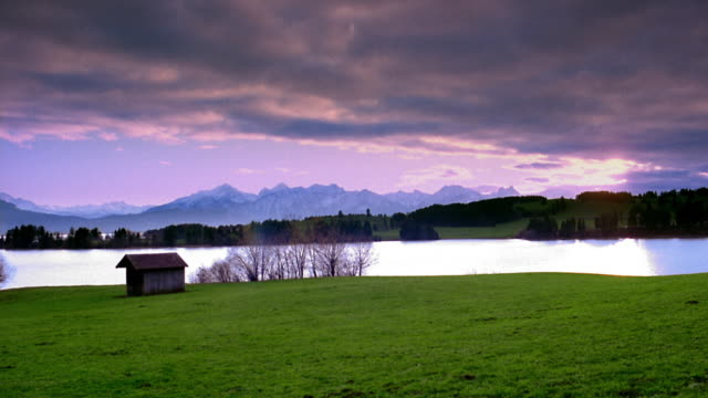 Wide shot time lapse clouds moving over lake with mountains in background and cabin in foreground at twilight / Fussen, Germany