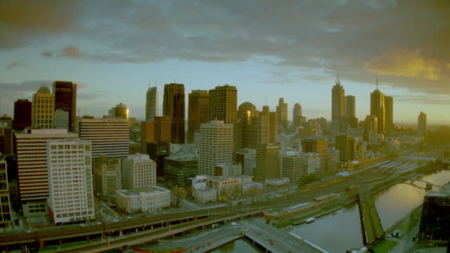 vidéos et rushes de wide shot time lapse clouds moving over melbourne skyline at sunrise / victoria, australia - 1990 1999