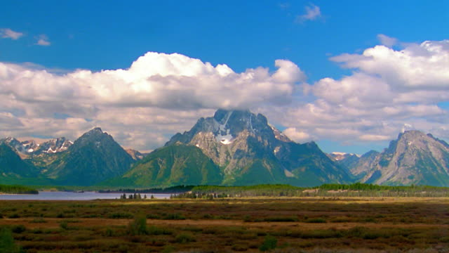 wide shot time lapse clouds moving over mt. moran and grand teton national park with plains in foreground / wyoming - mt moran stock videos & royalty-free footage