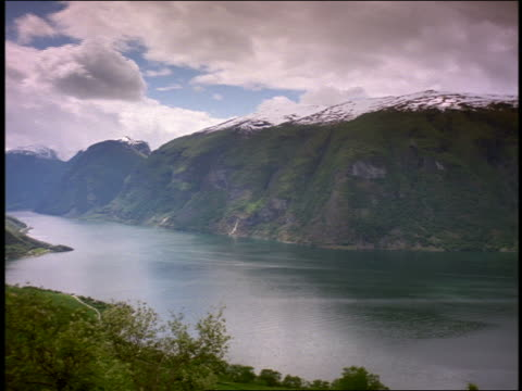 wide shot time lapse PAN clouds moving over river + valley surrounded by mountains / Aurlands Fjord, Norway