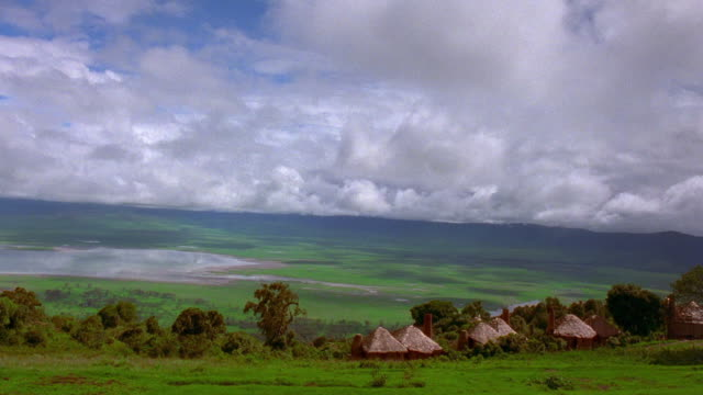 Wide shot time lapse clouds moving over valley with straw huts and lake / Serengeti National Park, Tanzania